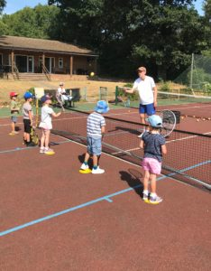 Our assistant Luke helping the mini red campers with their volleys